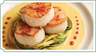 Pan-seared scallops over a bed of colorful peeled peppers, with plate dressing